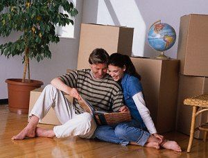 Man and woman looking at photo album with stack of boxes behind them