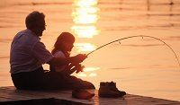 A father and daughter fishing during a sunset